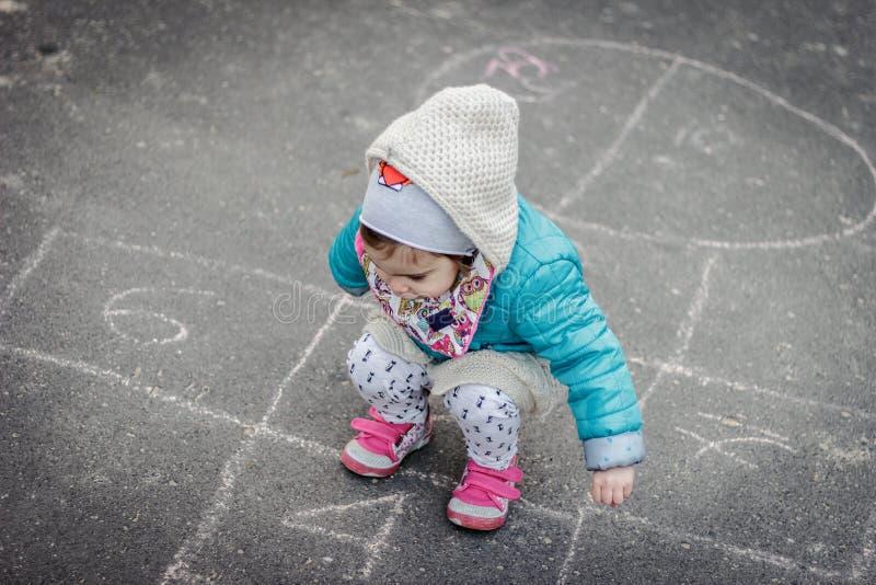 演奏跳房子的小和俏丽的女孩 免版税图库摄影
