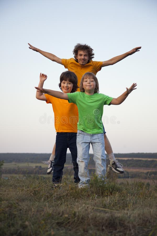 演奏跳跃在夏天日落草甸的孩子现出轮廓 免版税图库摄影