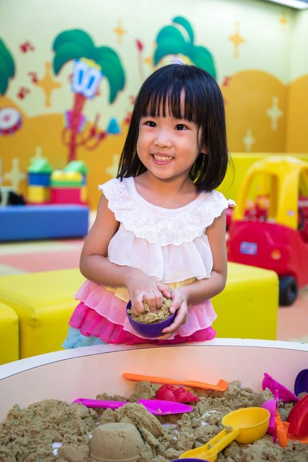 演奏运动沙子的愉快的亚裔中国小女孩室内 免版税图库摄影