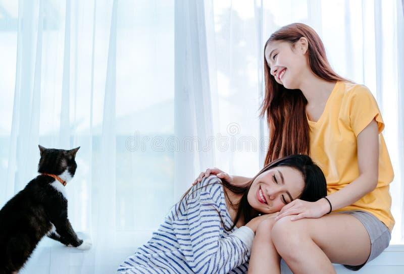 演奏逗人喜爱的猫宠物的同性亚裔女同性恋的夫妇恋人 免版税图库摄影