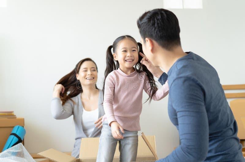 演奏逗人喜爱的矮小的女儿的父亲做在纸板箱,年轻亚洲家庭孩子的骑马获得乐趣在新房客厅 库存图片