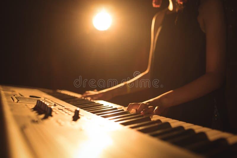 演奏钢琴音乐节的女性音乐家的中间部分 免版税库存照片