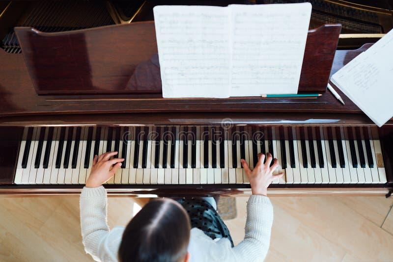 演奏钢琴顶视图的女孩 免版税库存照片