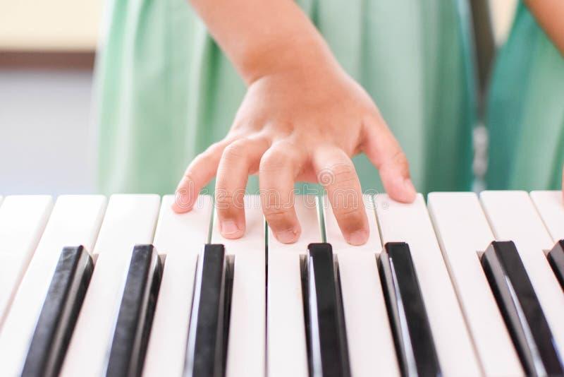演奏键盘的手孩子 免版税图库摄影