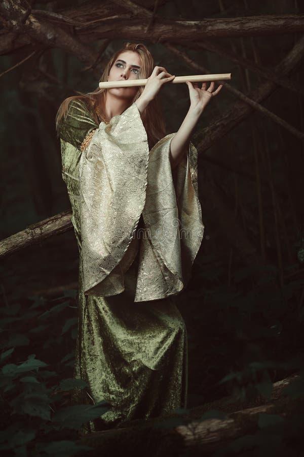 演奏长笛的小精灵似的公主 库存照片
