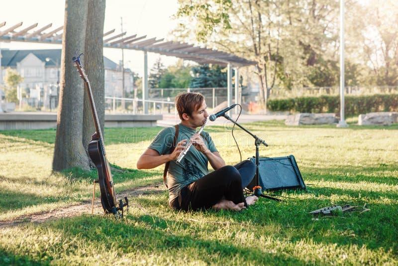 演奏长笛的白种人男性音乐家在公园外面夏天日落的 免版税库存图片