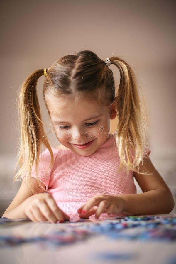 演奏难题的女孩 女孩使用的一点 黑色接近的耳机图象软绵绵地查出话筒填充白色 库存照片