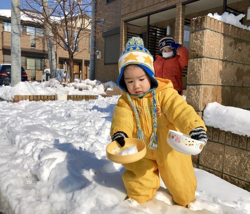 演奏雪和穿黄色孩童用防雪装的年轻男孩 免版税库存照片