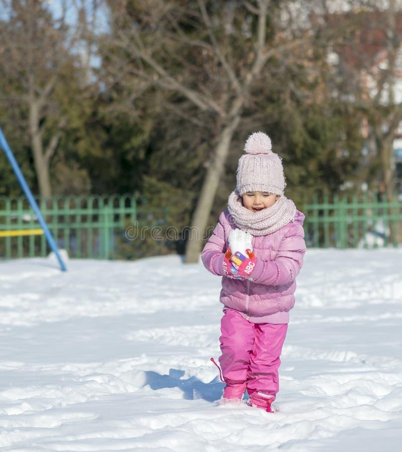 演奏雪年轻人的女孩 免版税图库摄影