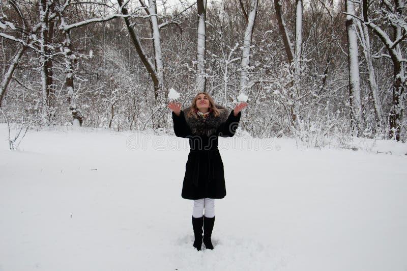 演奏雪球的一件黑外套的快乐的女孩在冬天森林里 库存照片