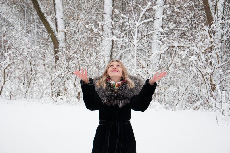 演奏雪球的一件黑外套的快乐的女孩在冬天森林里 免版税库存图片