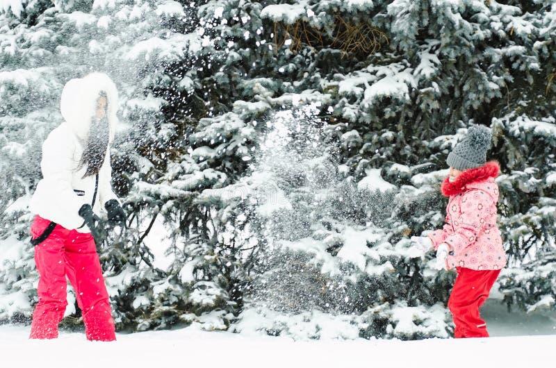 演奏雪球的少妇和她的女儿在冬天森林妇女投掷雪 免版税库存照片
