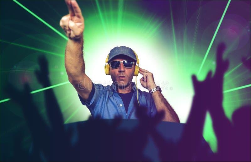 演奏音乐的凉快的节目播音员在夜总会混合的techno歌曲的党事件在激光和一刹那光背景欢呼用手 库存照片