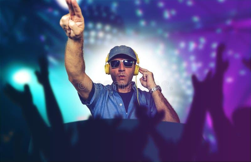 演奏音乐的愉快和凉快的DJ在夜总会混合的techno歌曲的党事件在激光和一刹那光背景欢呼与 免版税库存照片