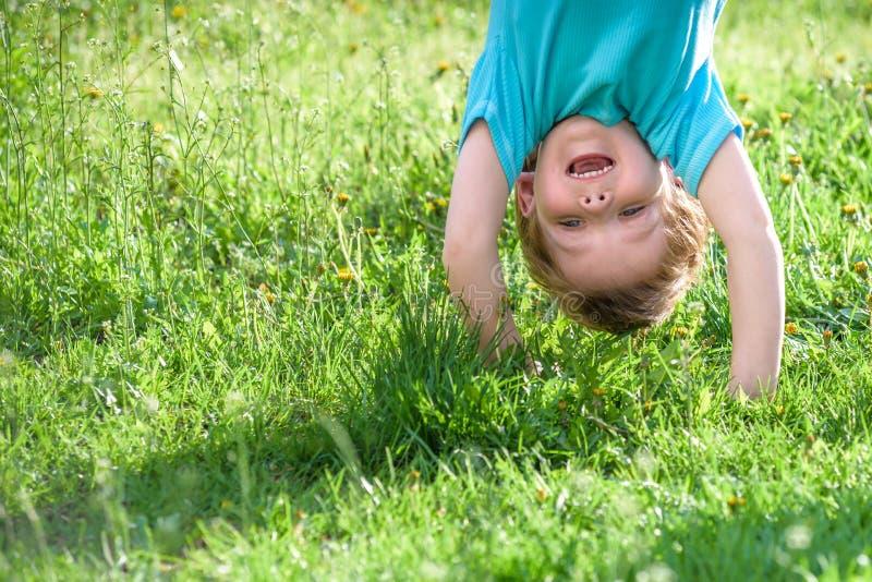 演奏颠倒的户外的愉快的孩子画象在夏天公园 免版税库存图片