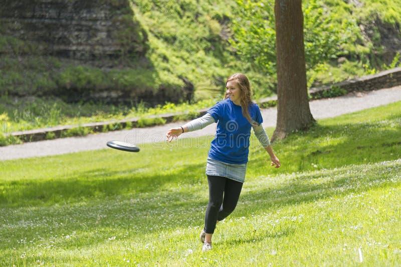 演奏飞碟的女孩在公园 库存照片