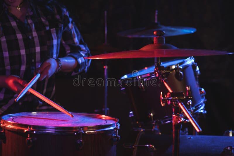 演奏鼓的女性鼓手设置在夜总会 免版税库存照片