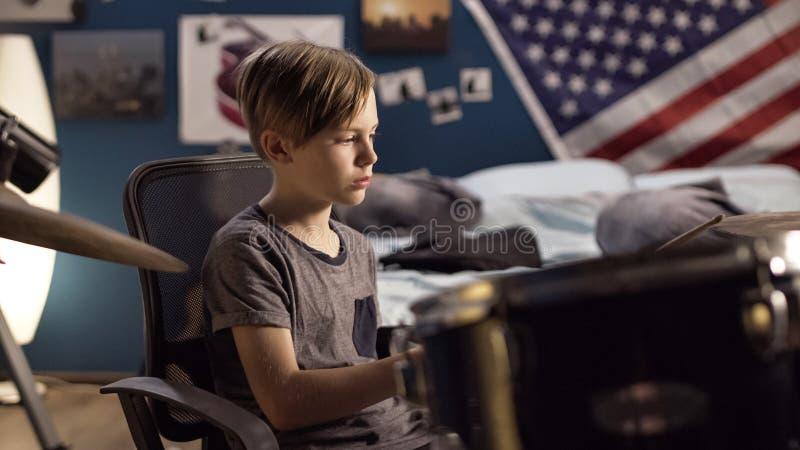 演奏鼓的男孩在卧室 免版税库存照片