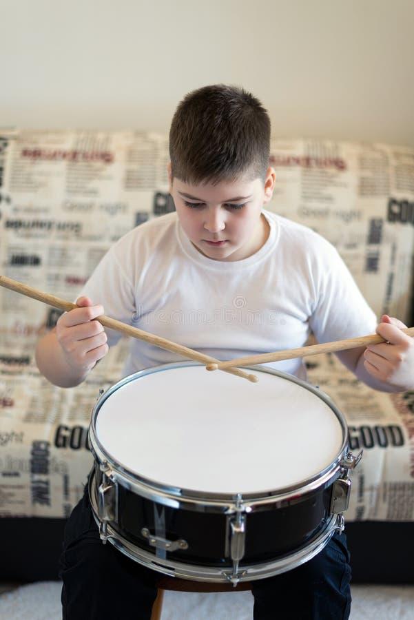 演奏鼓的男孩少年在屋子里 免版税库存图片