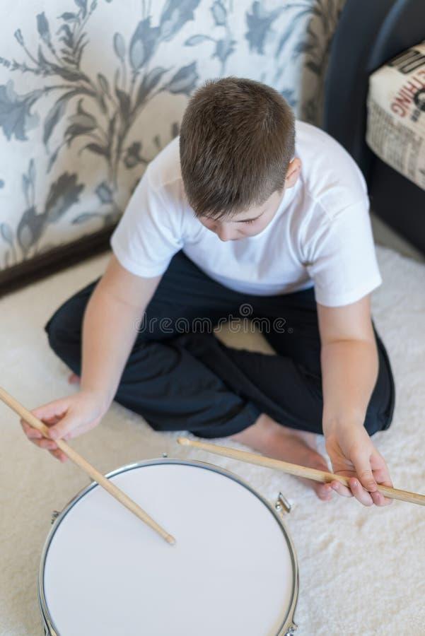 演奏鼓的男孩少年在屋子里 库存图片