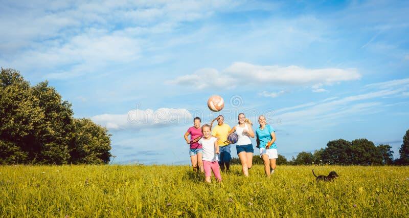 演奏,跑和做体育的家庭在夏天 库存照片