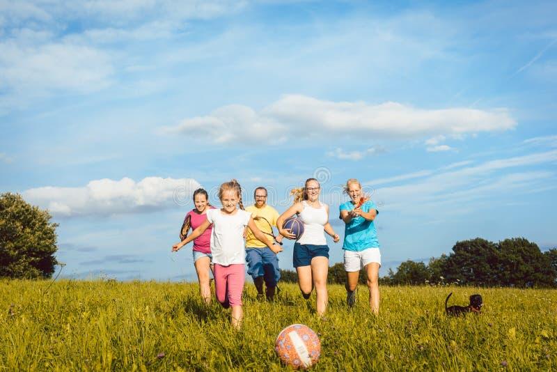 演奏,跑和做体育的家庭在夏天 免版税库存照片