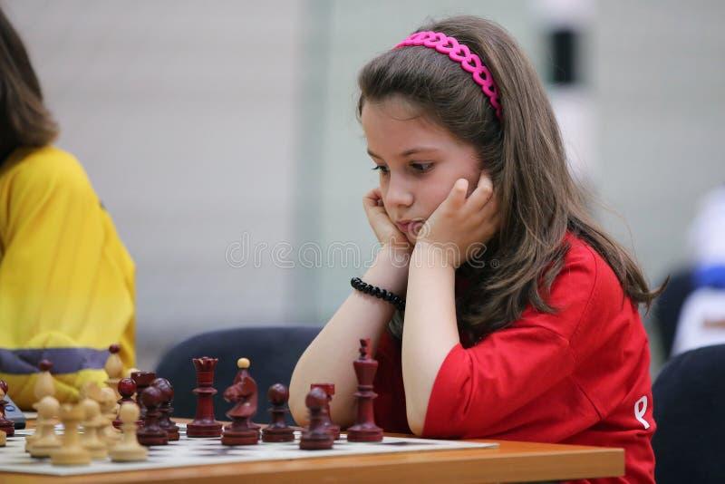演奏年轻人的棋女孩 免版税图库摄影