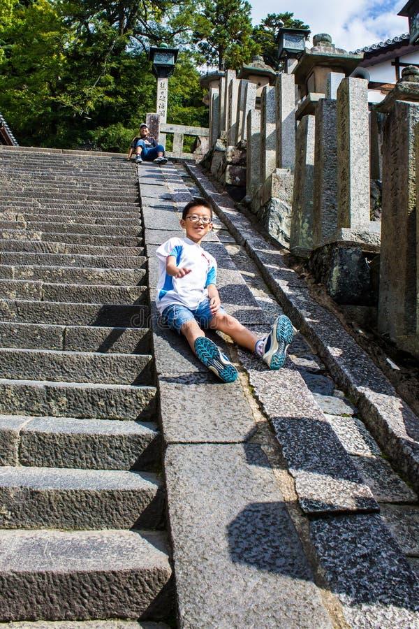 演奏滑倒从一石stairca的边缘的愉快的孩子 免版税库存照片
