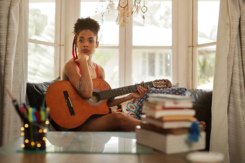 演奏经典吉他组成的音乐的妇女在她的屋子里 免版税库存照片