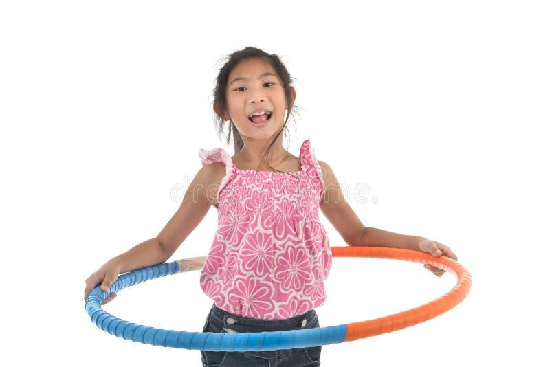 演奏hulahoop的愉快的矮小的亚裔儿童女孩画象打开  免版税库存图片