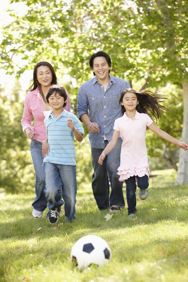 演奏soccerl的亚洲家庭在公园 免版税库存照片