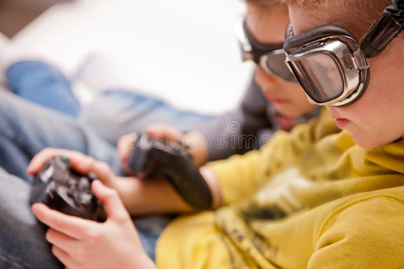 演奏wideogames的两个孩子假装作为飞行员 库存图片