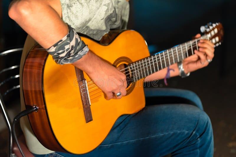 演奏yellowe的人一个声学吉他特写镜头 免版税库存照片