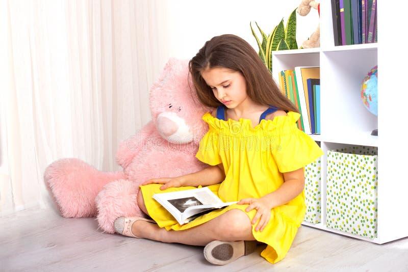 演播室佩带黄色sundress的射击了女孩坐书橱的地板有一个大桃红色玩具熊的并且读  免版税库存照片