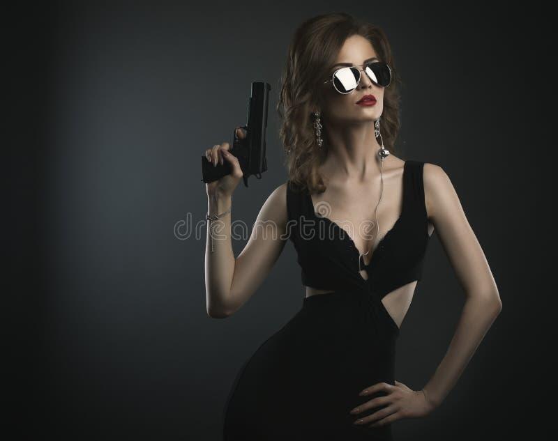演播室在黑暗的拿着枪的背景年轻秀丽妇女射击了 免版税库存图片