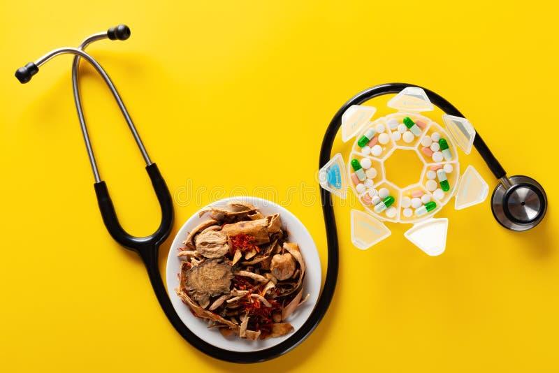 演播室射击中国草本医学和药片包裹与在黄色的一个听诊器 免版税图库摄影