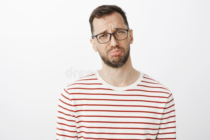 演播室射击了有胡子的成熟阴沉的人在玻璃,噘嘴和哭泣,抱怨对朋友的男朋友 免版税库存图片