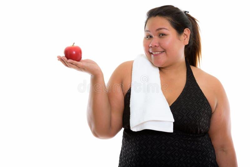 演播室微笑和拿着r的被射击年轻愉快的肥胖亚裔妇女 免版税库存图片
