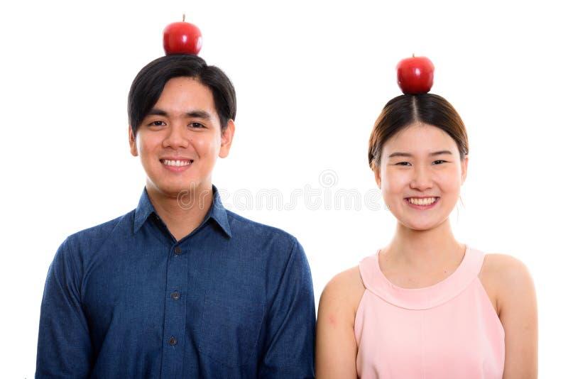 演播室微笑用红色苹果o的被射击年轻愉快的亚洲夫妇 库存图片