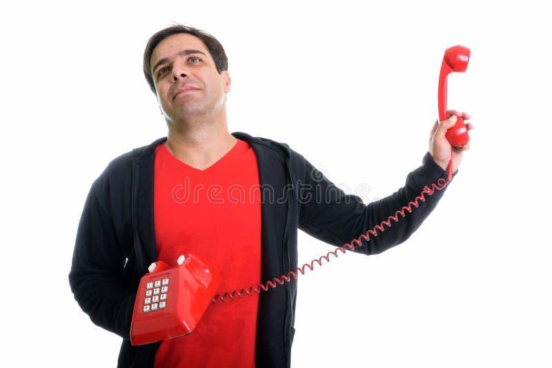 演播室拿着老telephon的被射击体贴的年轻波斯人 免版税库存图片