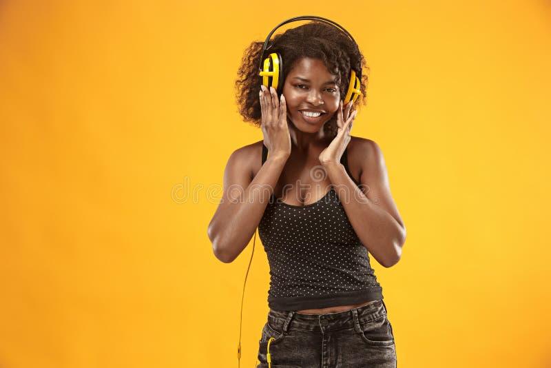 演播室画象可爱的卷曲女孩愉快微笑在photoshoot期间 有浅褐色的皮肤的惊人的非洲妇女 库存照片