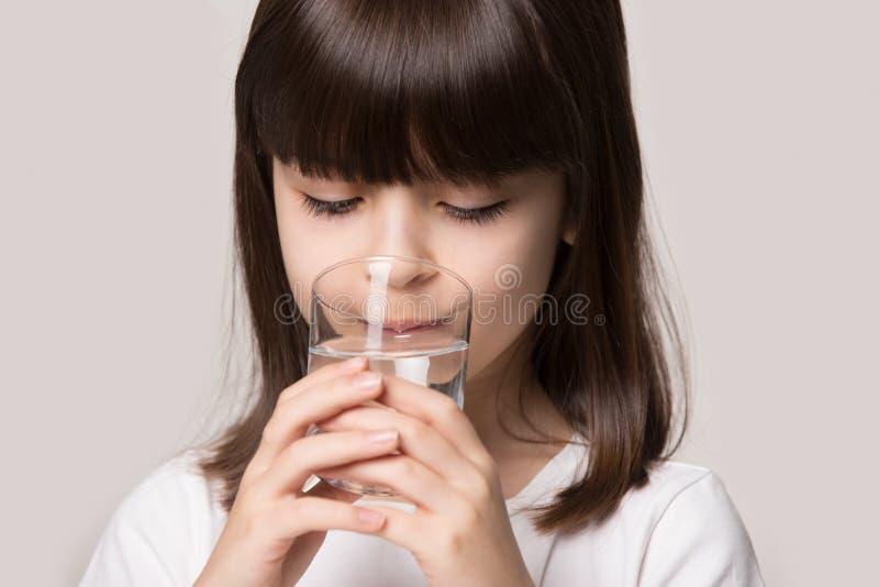 演播室画象女孩的关闭拿着玻璃饮用水 免版税库存图片