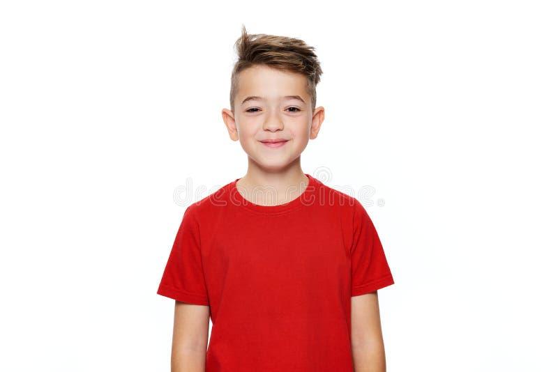 演播室画象的可爱的年轻十几岁的男孩腰部被隔绝在白色背景 看与微笑的帅哥照相机 库存照片