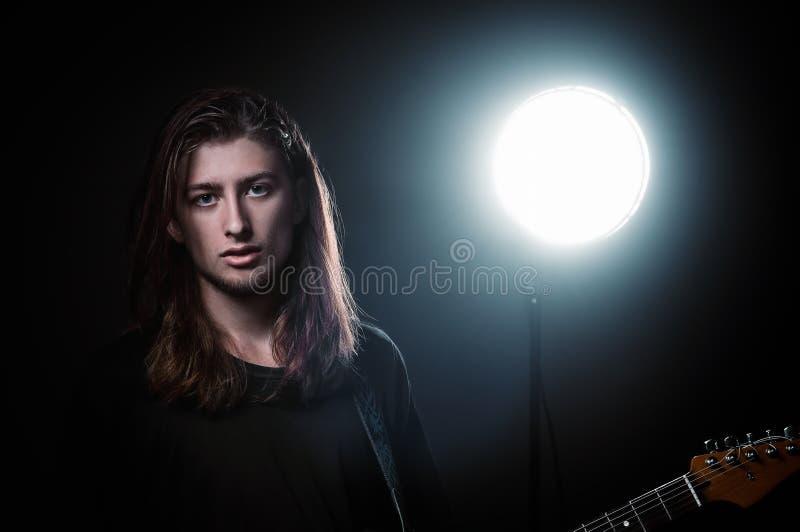 演播室画象:有电吉他的英俊的长发年轻人岩石音乐家 免版税图库摄影