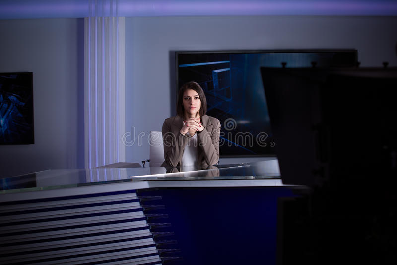 演播室的年轻美丽的深色的电视主持人在活广播期间 编辑的女性电视主任在演播室 库存图片