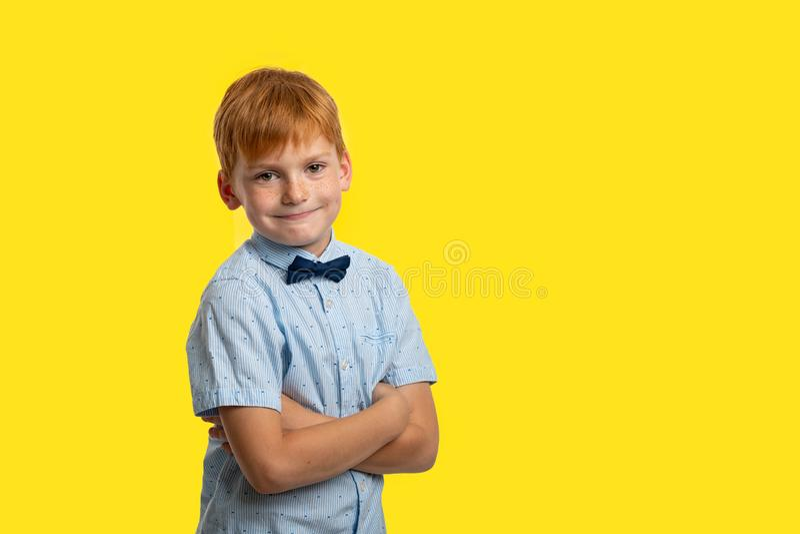 演播室穿有弓的被射击一个微笑的红头发人男孩蓝色T恤杉反对与拷贝空间的黄色背景 库存图片
