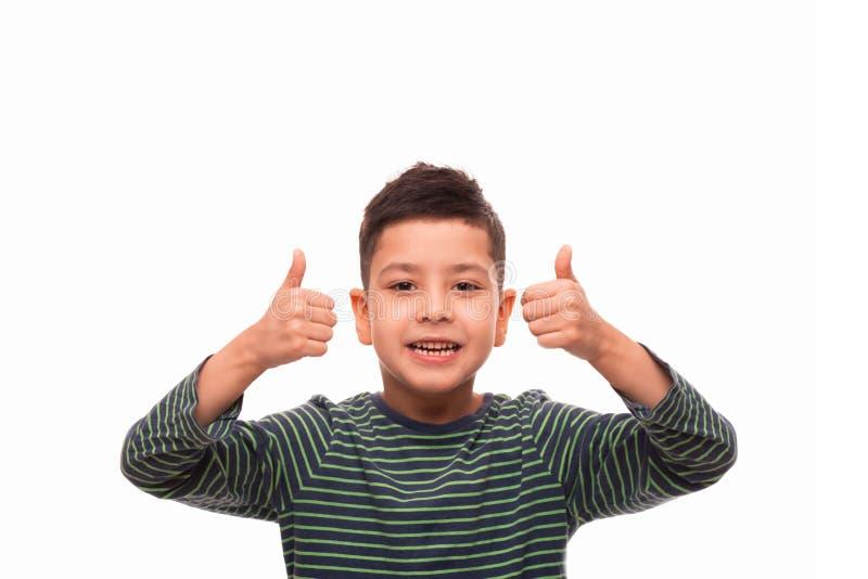 演播室穿绿色镶边衬衣的射击了男孩civing您一个满意的姿态,隔绝与拷贝空间 免版税库存图片