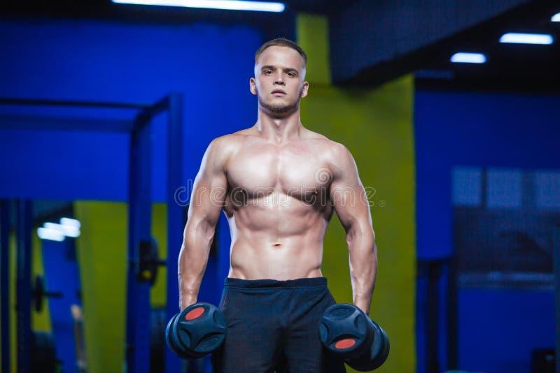 演播室被射击一个男性模型在两只手中的举行哑铃在健身房 解决赤裸上身的肌肉的人 健康和 免版税库存图片