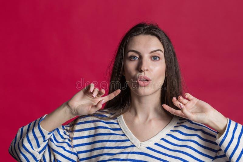 演播室被射击一可爱的美女被隔绝对空的红色演播室墙壁 免版税库存图片