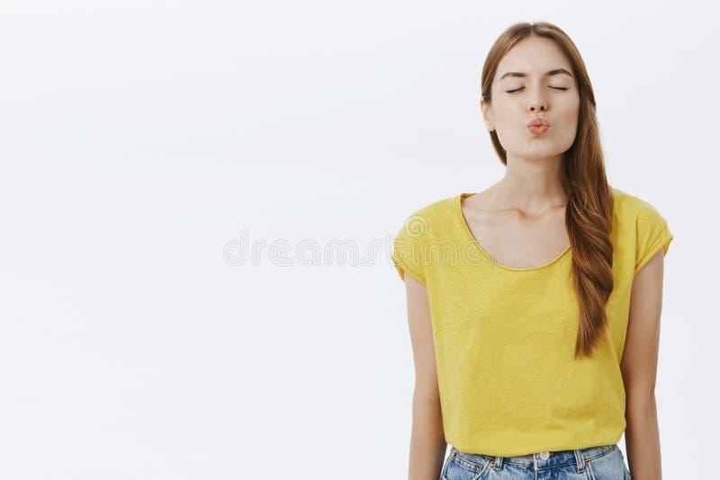 演播室被射击在黄色T恤杉的有吸引力的热情的时髦的女性模型有红色折叠嘴唇的头发关闭的眼睛的 免版税图库摄影